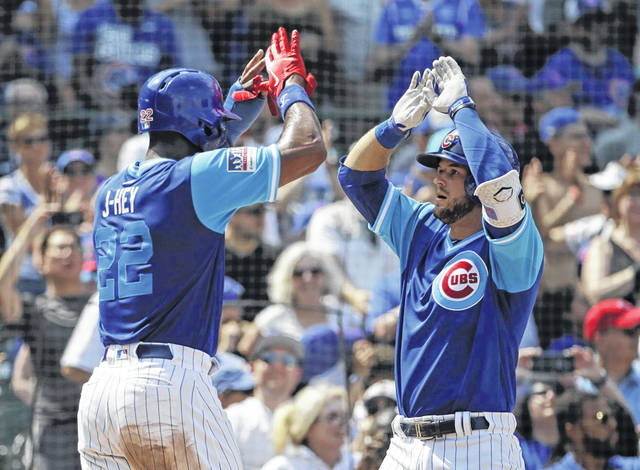 David Bote, right, of the Chicago Cubs, celebrates with Jason Heyward after hitting a two-run home run during the third inning of a baseball game against the Cincinnati Reds, Sunday at Wrigley Field.