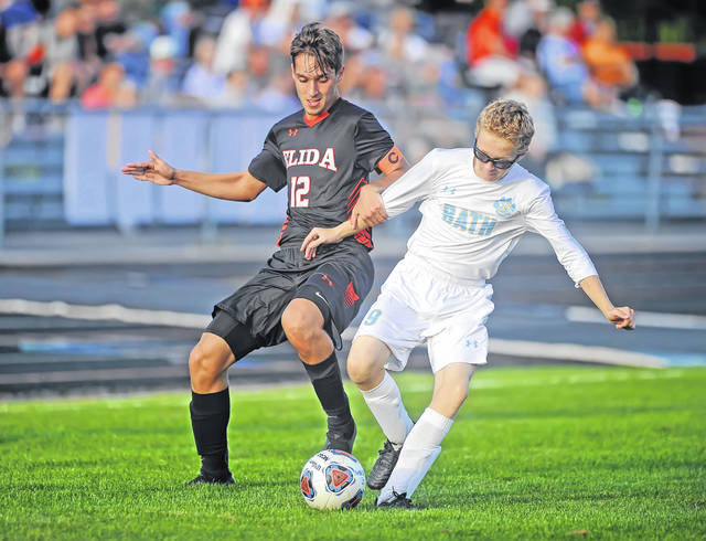 Elida's Corbin Fingerle, left, and Bath's Noah Kindig battle for the ball during Thursday night's match at the Elida Sports Complex. See more match photos at LimaScores.com.