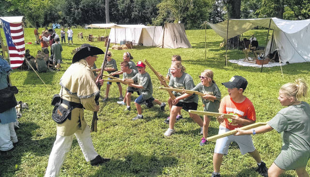 War of 1812 militia reenactor Aaron Owens teaches elementary school children how to fight with a rifle.