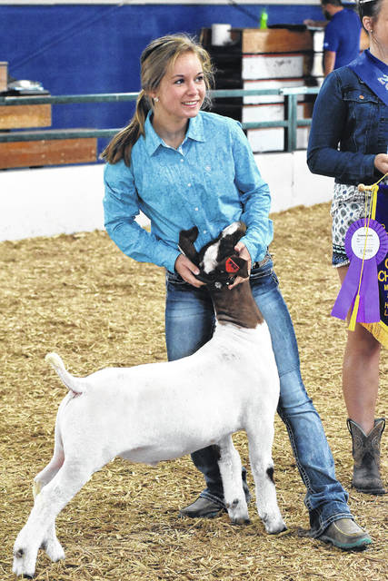 Payton Halker, of Future Shepherds Club, shows her Grand Champion goat at last year's auction. It sold for $2,200.