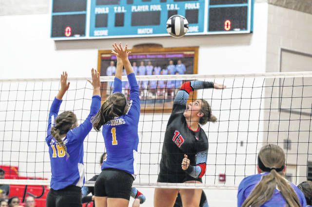 Brianna Altenberger, left, and Abby Buettner of Delphos St. John's go up to block the spike of Lima Central Catholic's Rosie Williams during Thursday night's match at LCC.