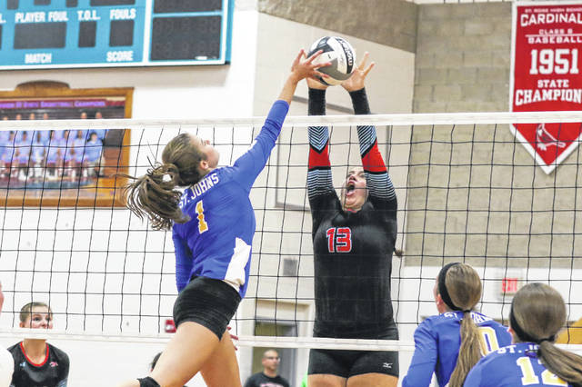Abby Buettner of Delphos St. John's has her spiked blocked by Lima Central Catholic's Rosie Williams during Thursday night's match at LCC. See more match photos at LimaScores.com.