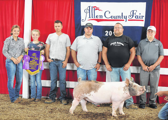 Grand Champion Market Swine and exhibitor Montana Hulsmeyer pose for a photo during Friday's livestock auction at the Allen County Fair.