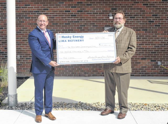 Jerry Miller, vice president of U.S. refining for Husky Energy, presents a $100,000 check to Joesph Brandesky, Ohio State-Lima interim dean and director, outside the Perry Webb Student Life Building Wednesday.