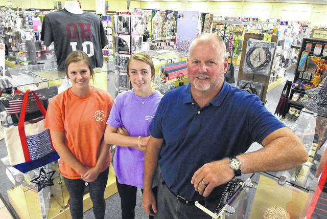 Steve Brunner, owner of Readmore's Hallmark in Lima, works in his store with his daughters, Maddie, left, and Kaitie.