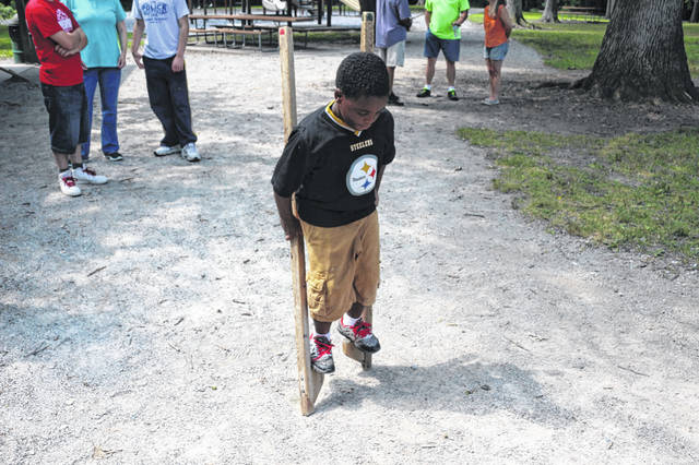 Taverrence Moore, 8, learns how to use stilts at the culmination of the See Me Now program, which was designed to teach kids STEM skills.