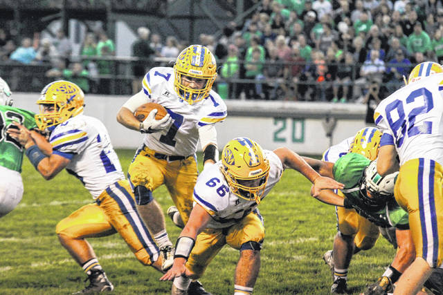 St. Mary's Sean Perry follows fullback Tyler Miller through a hole against Celina's defense on Friday night.   Levi A. Morman | The Lima News