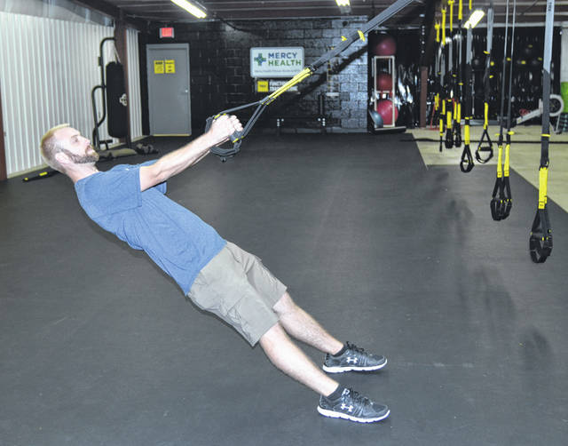Bluffton Family Recreation Executive Director Daniel Tinch demonstrates how to use the TRX Pro4 System, one of the new pieces of equipment added to the new Mercy Health Fitness Studio at Bluffton Family Recreation.