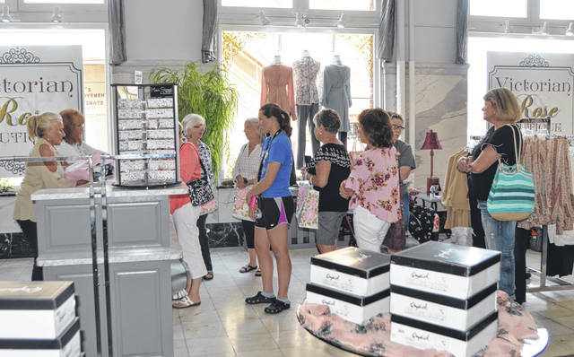 Customers stand in line to purchase items during the grand opening of Victorian Rose Boutique on 249 N Main St., Tuesday.