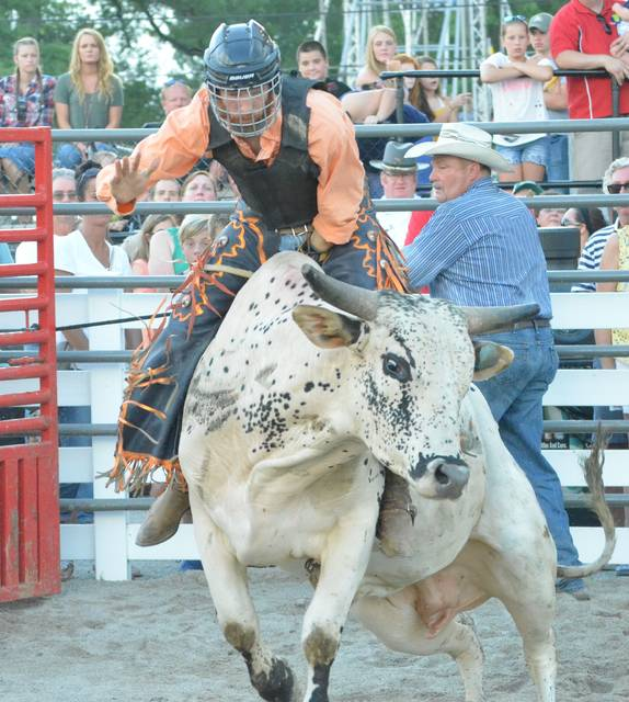"Bull rider Jesse James, of Celina, begins his ride on a bull named Twister Friday during the Auglaize County Fair bull riding competition at the grandstand. ""The second I hear that buzzer my next thought is 'How do I get off?' It's a lot trickier than it looks,"" James said after completing his 8-second ride."