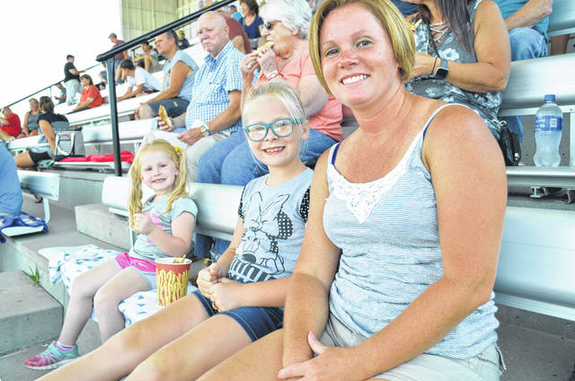 Demolition derby fans Jennifer Burden (right) Mallory Burden (center), 7, and Allie Burden, 3, were seated in the Auglaize County Fair Grandstand at 5:30 p.m. Thursday waiting for the demolition derby to begin at 7:30 p.m.