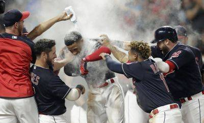 Cleveland Indians' Francisco Lindor, center, is welcomed by teammates after he hit a walk-off three-run home run against the Minnesota Twins during Wednesday's game in Cleveland. (AP photo)