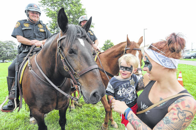 "Two year-old Klayton Godfrey and his mother Logan of Lima pet Allen County Mounted Posse Capt. Joel Gillette's horse ""Tank"" during National Night Out at the Allen County Fairgrounds on Tuesday evening."