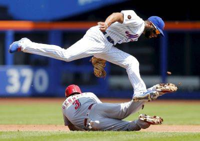 Cincinnati's Scooter Gennett is tagged out at second base by New York Mets' Amed Rosario during a first inning steal attempt during Wednesday's game in New York. (AP photo)