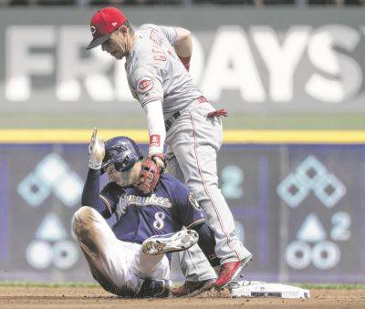 Cincinnati's Scooter Gennett catches the Brewers' Ryan Braun off of second base to tag him out during Wednesday's game in Milwaukee.