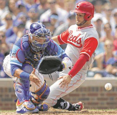 Cincinnati's Eugenio Suarez slides safely into home while the Cubs' Willson Contreras waits for the throw during the fourth inning of Saturday's game in Chicago.