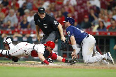 Reds catcher Tucker Barnhart, dives to tag out Milwaukee's Travis Shaw during the fourth inning of Tuesday night's game in Cincinnati. Home plate umpire Bill Welke, rear, makes the call. (AP photo)