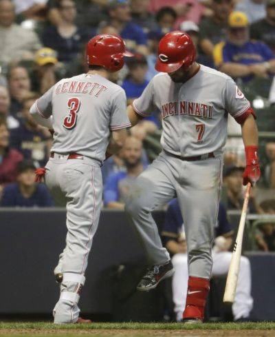 Cincinnati's Scooter Gennett celebrates with Eugenio Suarez (7) after hitting a home run during the ninth inning of Tuesday night's game against the Brewers in Milwaukee. (AP photo)