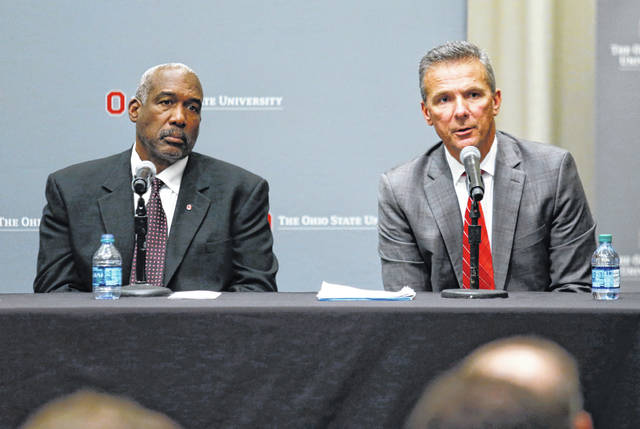 "FILE - In this Aug. 22, 2018, file photo, Ohio State football coach Urban Meyer, right, answers questions as athletic director Gene Smith listens during a news conference in Columbus, Ohio. What got Meyer in hot water? The suspended coach puts it this way: ""My fault was in not taking action sooner against a troubled employee about his work-related issues."" That now-fired assistant coach had been accused of past spousal violence as well as embarrassing sexual conduct, drug abuse and financial irresponsibility. Outside investigators found some of that affected his work life. Meyer's comments about handling that and the ensuing debate about his punishment point to a bigger question in college athletics: To what extent are coaches responsible for policing their staff's off-field behavior? (AP Photo/Paul Vernon, File)"