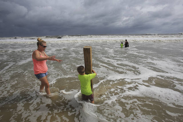Lauren Dueitt, left, and John Payne, 6, right, play in the high tide waters caused by Tropical Storm Gordon on Tuesday, Sept. 4, 2018, in Dauphin Island, Ala. (AP Photo/Dan Anderson)