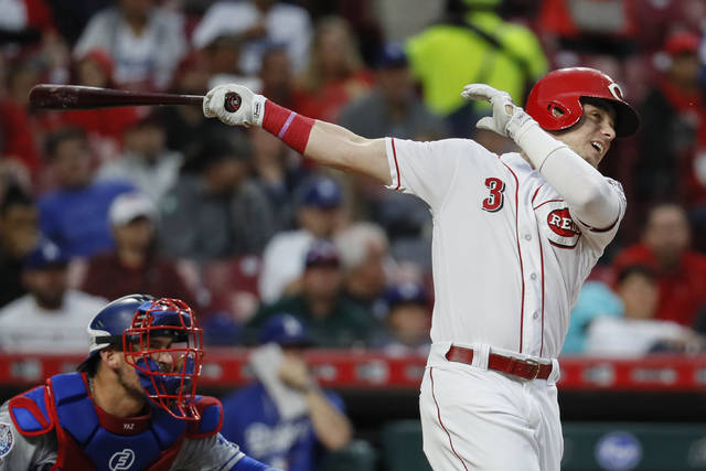 Cincinnati Reds' Scooter Gennett hits an RBI single off Los Angeles Dodgers starting pitcher Alex Wood in the first inning of a baseball game, Monday in Cincinnati.