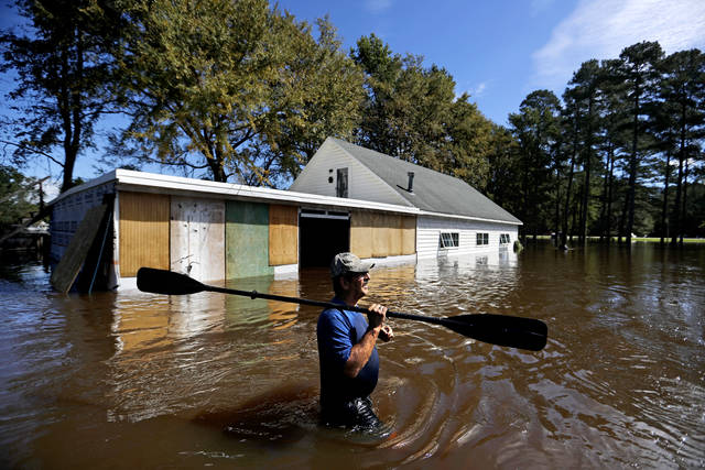 Kenny Babb retrieves a paddle that floated away on his flooded property as the Little River continues to rise in the aftermath of Hurricane Florence in Linden, N.C., Tuesday, Sept. 18, 2018. (AP Photo/David Goldman)
