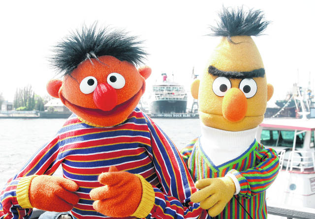 """Ernie and Bert of """"Sesame Street"""" pose in front of the Queen Mary II in the harbor of Hamburg, Germany. The producers of """"Sesame Street"""" tweeted Tuesday that Bert and Ernie are not gay in response to an interview published Sunday with a former writer for the show who said he considered the puppets lovers."""