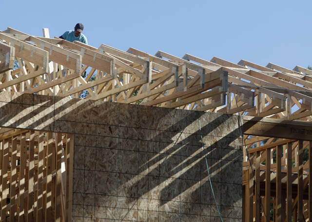 FILE- In this Thursday, Aug. 30, 2018, file photo, a worker toils on a new home under construction in Denver. On Wednesday, Sept. 19, the Commerce Department reports on U.S. home construction in August. (AP Photo/David Zalubowski, File)