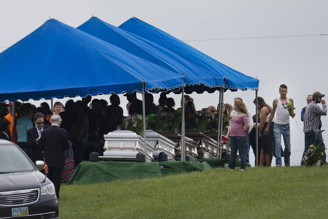 FILE – In this May 3, 2016, file photo, mourners gather around caskets for six of the eight members of the Rhoden family found shot April 22, 2016, at four properties near Piketon, Ohio, during funeral services at Scioto Burial Park in McDermott, Ohio. The Ohio Supreme Court has sided with a newspaper seeking to view autopsy reports and photos in the still-unsolved slayings of the eight Rhoden family members. The court ruled unanimously Wednesday in favor of the Cincinnati Enquirer, saying Ohio law allows reporters to view preliminary autopsy and investigative notes and findings, and photographs.