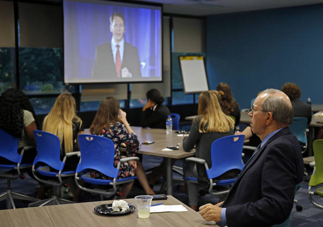 Former Ohio Gov. Bob Taft, far right, joins students for a watch party during a debate between Republican gubernatorial candidate, Ohio Attorney General Mike DeWine and Ohio Democratic gubernatorial candidate Richard Cordray, shown on the screen, at the University of Dayton, Wednesday, Sept. 19, 2018, in Dayton, Ohio. (AP Photo/Gary Landers)