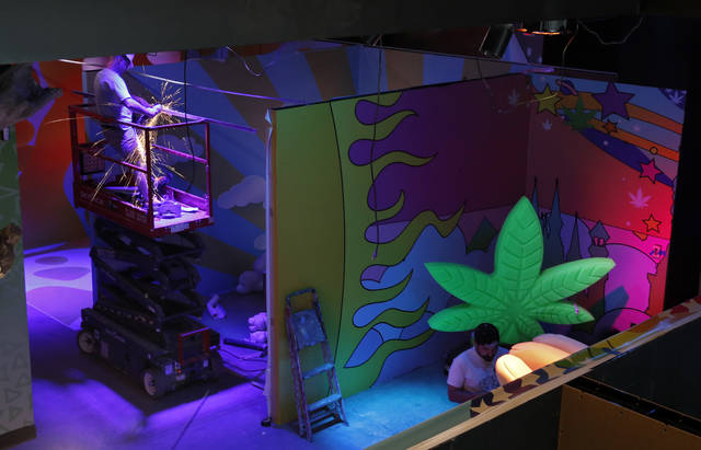 In this Tuesday, Sept. 18, 2018 photo, workers finish exhibits at the Cannabition cannabis museum in Las Vegas. The museum celebrating all things cannabis with displays that include a glass bong taller than a giraffe and huggable faux marijuana buds is the newest tourist attraction in Las Vegas. (AP Photo/John Locher)