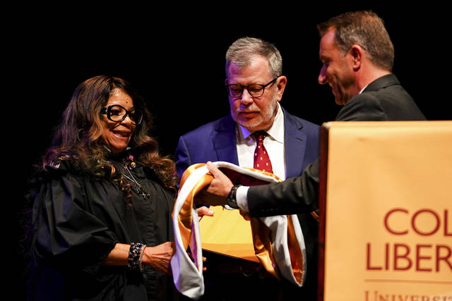 Prince's sister, Tyka Nelson, left, stood beside University of Minnesota President, Eric Kaler, center, as she was presented the school's highest honor, the Doctorate of Humane Letters, and sash by Kaler and Regent Darrin Rosha, right, for the late rock star Prince, at the Ted Mann Concert Hall Wednesday, Sept. 26, 2018, in Minneapolis. The University of Minnesota awarded Prince an honorary degree to recognize his influence on music and his role in shaping his hometown of Minneapolis. (Aaron Lavinsky/Star Tribune via AP)
