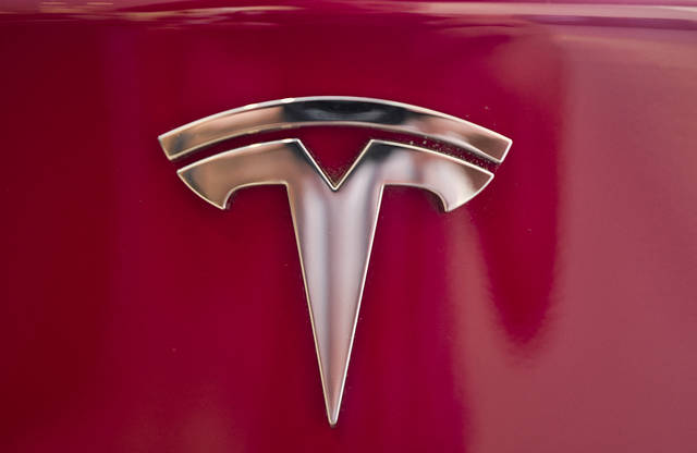FILE - This Aug. 8, 2018 file photo shows the Tesla emblem on the back end of a Model S in the Tesla showroom in Santa Monica, Calif. Tesla investors have taken a wild ride as Wall Street values the promise of one of the world's leading electric car makers, the hurdles the company faces as it tries to become a world-class manufacturer, and a mercurial CEO who can get the market buzzing with a single tweet.  (AP Photo/Richard Vogel, File)