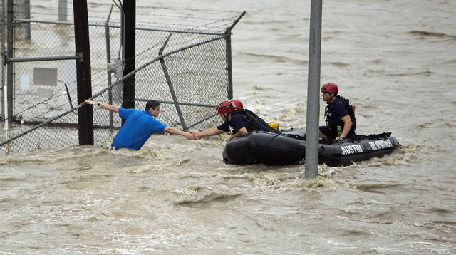 FILE - In this May 25, 2015 file photo, rescue personnel grab the the hand of a man stranded in rushing water at the northwest corner of Lamar Boulevard and 15th Street in Austin, Texas. In September 2018, The Associated Press has found a manipulated version of this photograph circulating on the Internet, which added a separate image President Donald Trump in the raft reaching out to the man in the floodwaters. (Alberto Martinez/Austin American-Statesman via AP)