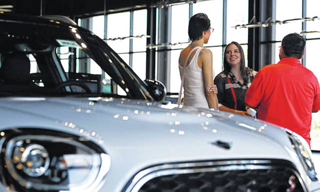 A salesperson, center, confers with two customers interested in the 2018 Countryman on display in the showroom of a Mini dealership in Highlands Ranch, Colo., in August. If you work with a good car salesperson, the shopping process can actually be fun, and you'll be more confident you're getting a good deal.