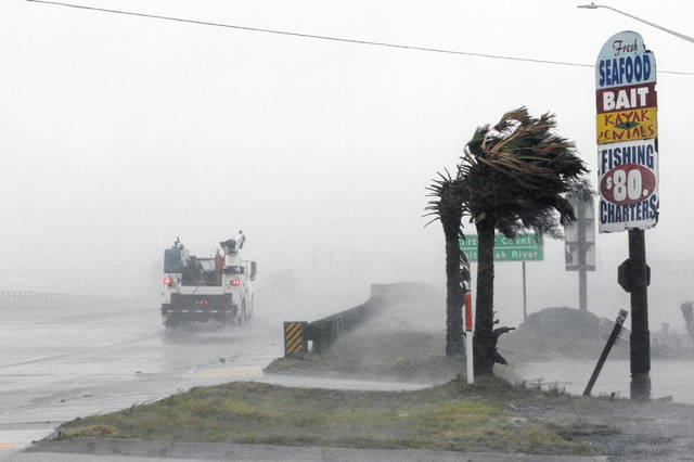 A work truck drives on Highway 24 as the wind from Hurricane Florence blows palm trees in Swansboro N.C., Thursday, Sept. 13, 2018.