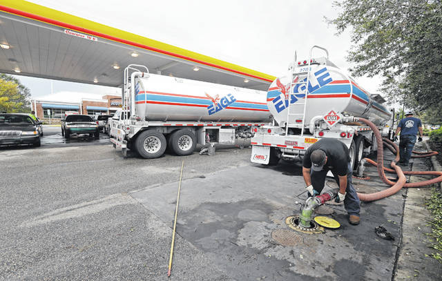 FILE- In this Sept. 17, 2018, file photo people wait in line as Travis Hall, right, and Brandon Deese, back, pump fuel from two tanker trucks at a convenience store in Wilmington, N.C. America's rediscovered prowess in oil production is shaking up old notions about the impact of higher crude prices on the U.S. economy.