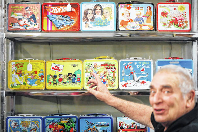 In this Friday, Sept. 21, 2018 photo, owner J. Louis Karp opens a case of vintage lunch boxes at Main Auction Galleries Inc., in downtown Cincinnati. Karp, a longtime auctioneer of Cincinnati-area estates has come upon a Baby Boomer delight: hundreds of vintage lunchboxes featuring the heroes of their childhood's comic books, TV shows, cartoon strips, movies and more.