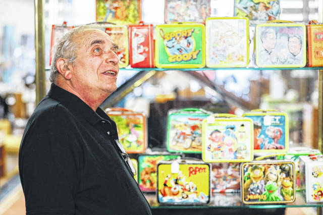 In this Friday, Sept. 21, 2018 photo, owner J. Louis Karp stands beside a case of vintage lunchboxes at Main Auction Galleries Inc., in downtown Cincinnati. Karp, a longtime auctioneer of Cincinnati-area estates has come upon a Baby Boomer delight: hundreds of vintage lunchboxes featuring the heroes of their childhood's comic books, TV shows, cartoon strips, movies and more.