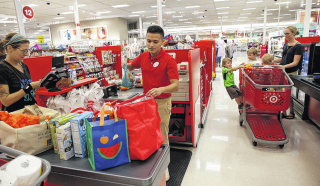 Cashier Kevin Cruz bags a customers order as Merideth Lembke and her four children line up to pay for their school supplies and groceries at the remodeled Super Target store in Broadview, Illinois, in July. Many stores, such as Target, are getting creative to lure people into seasonal jobs.