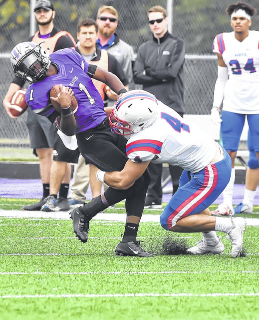 Bluffton's Plummine Gardner, a Perry graduate, fights for yards against Hanover's Kyle Treber during Saturday's game at Dwight Saizman Stadium in Bluffton.