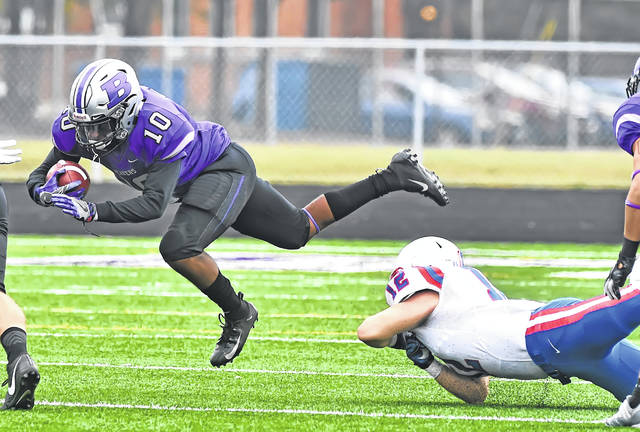 Hanover's Sean Fleming trips up Bluffton's DeAngelo Woods, an Elida grad, during Saturday's game at Dwight Saizman Stadium in Bluffton.