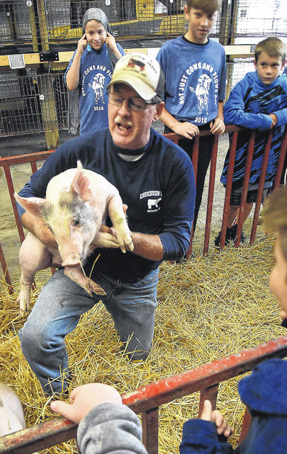 Jackson Purk, 10, a fourth-grader at Lincolnview Elementary School, plugs his ears as a piglet squeals during Cows and Plows Tuesday. Holding the piglet is Mike Schumm, an area farmer who talked with students about livestock production.