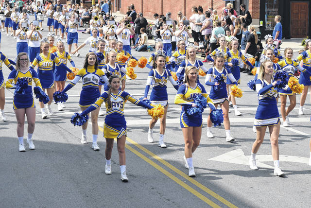 Cheerleaders march in last year's Delphos Canal Days parade. Tents are going up at the former Cintas lot, but the parade will be on the regular route. Fresh paving is preventing tents from being erected in the usual place.