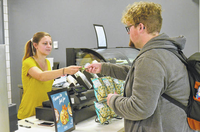 Ohio State University-Lima freshman Trenton Berger, of Continental (right), retrieves his card from OSU senior Emali Sroufe, a student employee, after placing an order at the new Starbucks at the new Perry Webb Student Life Building. Nutrien Lima Nitrogen donated $75,000 to OSU Friday to support the programs, activities and staffing of the new building.