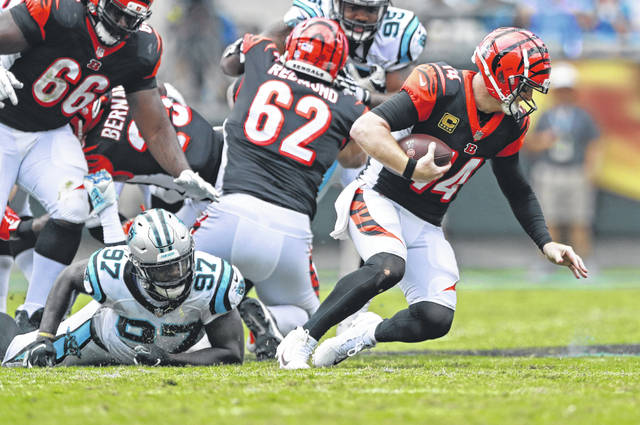 Cincinnati Bengals' Andy Dalton (14) is sacked by Carolina Panthers' Mario Addison (97) during the second half of an NFL football game in Charlotte, N.C., Sunday.