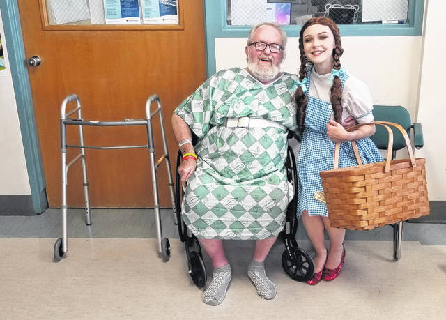 """Sydney Hartford, dressed as Dorthy Gale in """"The Wizard of Oz,"""" visits Pat Bolling a patient at Mercy Health-St. Rita's Medical Center, Monday."""