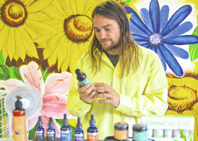 Dr. Joshua Hayes organizes the layout of a number of CBD products he sells as at Garden Grove Holistic in Shawnee Township. Hayes argues the Ohio State Board of Pharmacy is legally wrong when it claimed hemp-derived CBD was illegal.