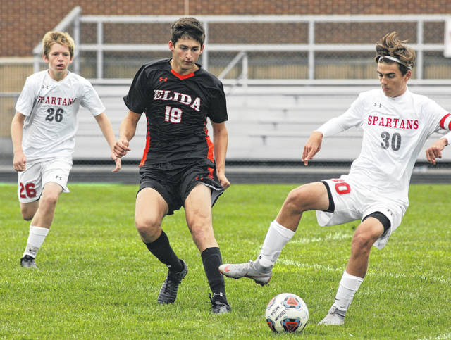 Lima Senior's Caden Fry (30) looks to keep the ball away from Elida's Logan Johnson during Saturday's match at Elida.