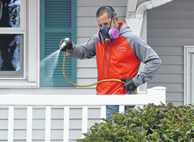 Craig Ruhe, of Tri-State Pest Solutions, sprays around the exterior of a home in Ottawa.